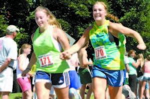 HAND IN HAND — Heading toward the finish line are Sierra Leavitt (left) and Kristina Morton, both of Naples,