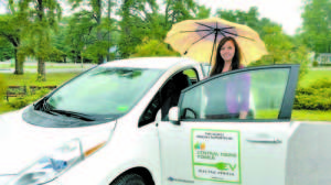 TOWN OF NAPLES SECRETARY — Kate Matthews had the chance to test drive an electric car on a rainy day. All last week, the Town of Naples got to borrow the Nissan Leaf from the Greater Portland Council of Governments (CPCOG). The first comment most people made about the vehicle is how quiet it is. (Photo Courtesy of Naples Town Manager Ephrem Paraschak)
