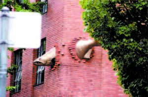 THIS FISH APPEARS to migrate through a brick building in Portland, Ore. The photo was snapped by Lynne Potter, who learned during her trip to the West Coast that in Seattle all buildings paid for with public funds are required to have statues. (Photo courtesy of Lynne Potter)